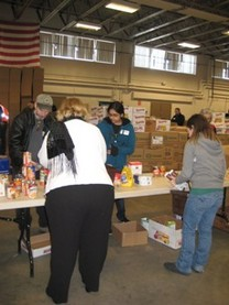 Volunteers begin sorting donated non-perishable food items as part of the 2010 Holiday Food Basket Project.