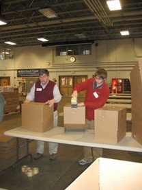 A father and son work side-by-side building boxes during the 2010 Holiday Food Basket Project.