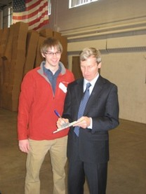 "An annual Holiday Food Basket Project tradition!  Governor John Lynch writes a 'Please excuse xxx"" from school today' note for one of our student volunteers!"
