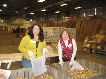 Volunteers help bag potatoes as part of the 2010 Holiday Food Basket Project.